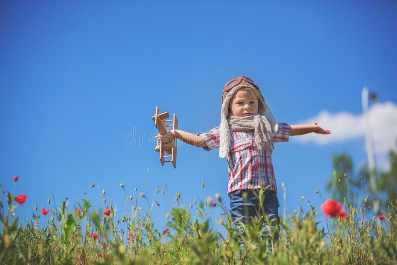 Piękny dzieciak, dziecko bawiące się samolotem w polu maku, słoneczne popołudnie zdjęcia stock