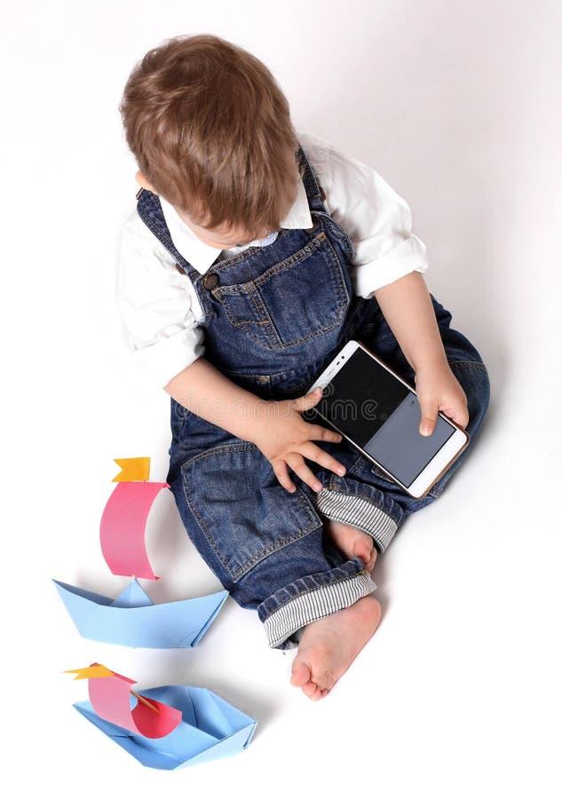 Pi?kny dziecko bawi? si? z m?drze telefonem odizolowywaj?cym na bia?ym tle obrazy stock