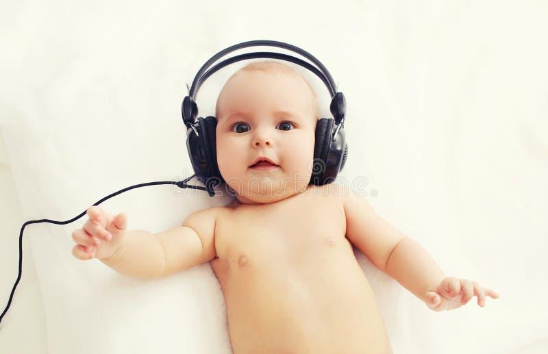 Piękny dziecko kłama na łóżku słucha muzyka w hełmofonach obrazy royalty free