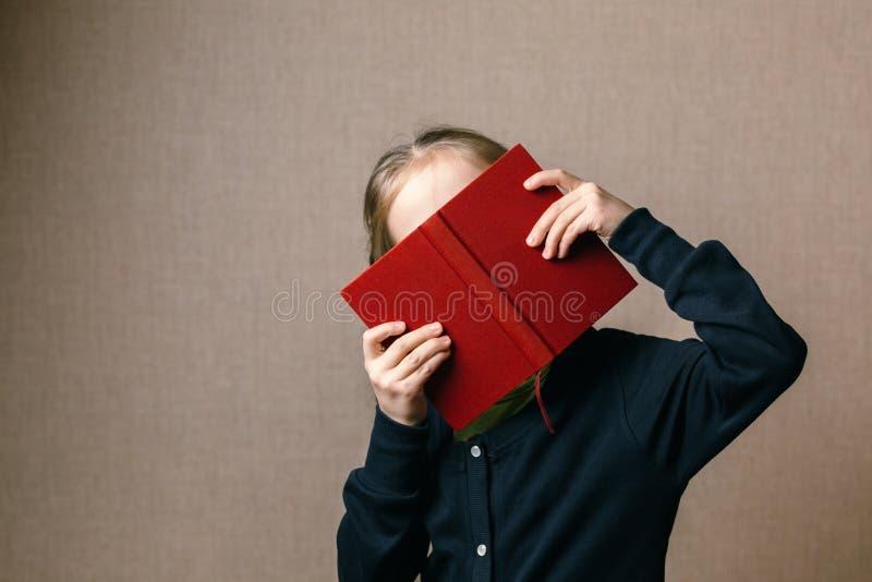 Piękny dziecko zakrywa jej twarz z książką obraz royalty free