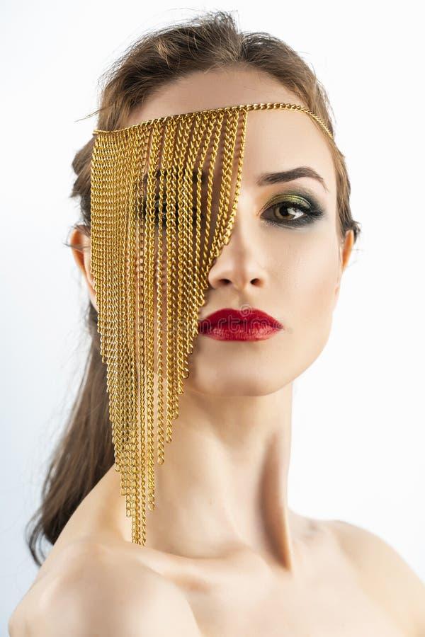 Piękny dziewczyna model z czerwonym warga makijażem i nagimi ramionami jest ubranym konceptualną mody biżuterię robić złoto łańcu obraz stock