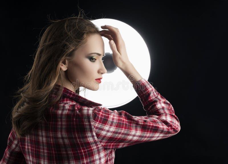 Piękny dziewczyna model z czerwonym warga makijażem i włosiany spływanie od wiatru, jest ubranym przypadkową szkockiej kraty kosz obrazy royalty free