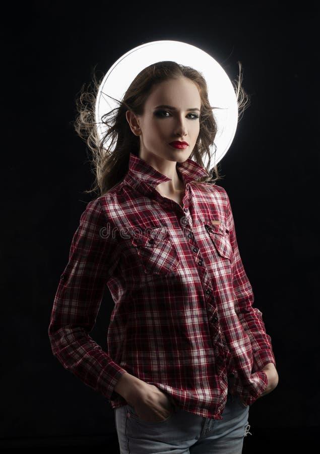 Piękny dziewczyna model z czerwonym warga makijażem i włosiany spływanie od wiatru, jest ubranym przypadkową szkockiej kraty kosz zdjęcie royalty free