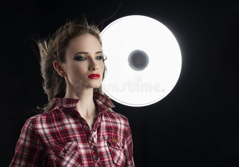 Piękny dziewczyna model z czerwonym warga makijażem i włosiany spływanie od wiatru, jest ubranym przypadkową szkockiej kraty kosz zdjęcia stock