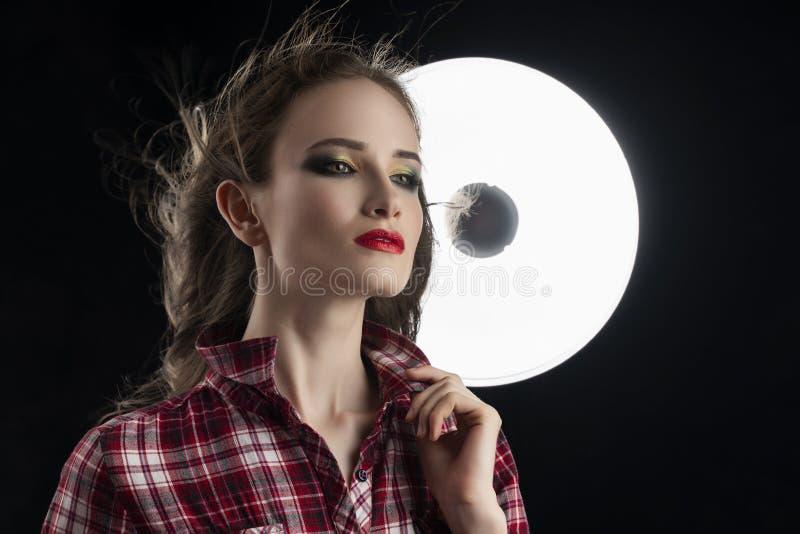 Piękny dziewczyna model z czerwonym warga makijażem i włosiany spływanie od wiatru, jest ubranym przypadkową szkockiej kraty kosz fotografia royalty free