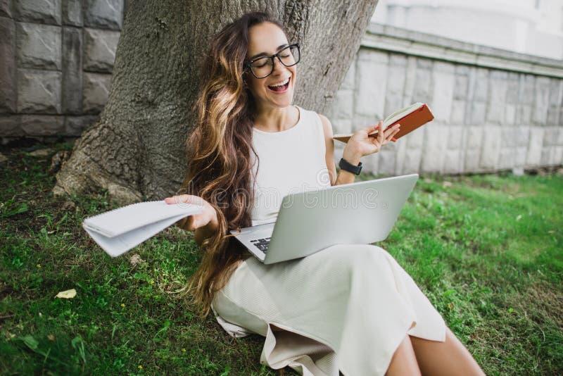 Piękny dziewczyna uczeń uczy się jej lekcje siedzi na trawie fotografia royalty free