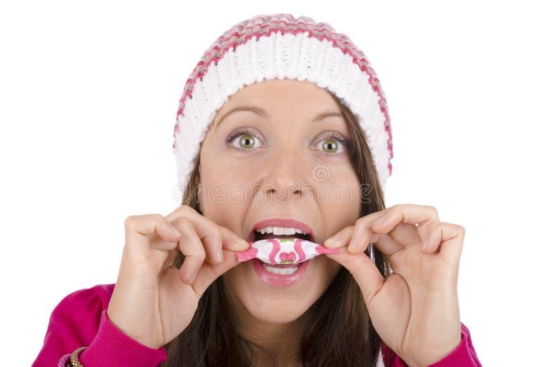 Piękny dziewczyny łasowania cukierek nad białym odosobnionym tłem zdjęcie royalty free