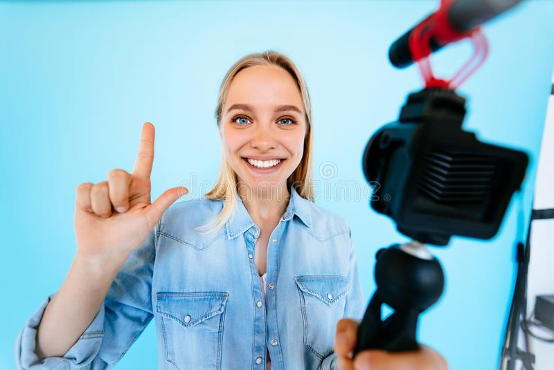 Piękny dziewczyny blogger ono uśmierza przy kamera odizolowywającym błękitnym tłem fotografia royalty free