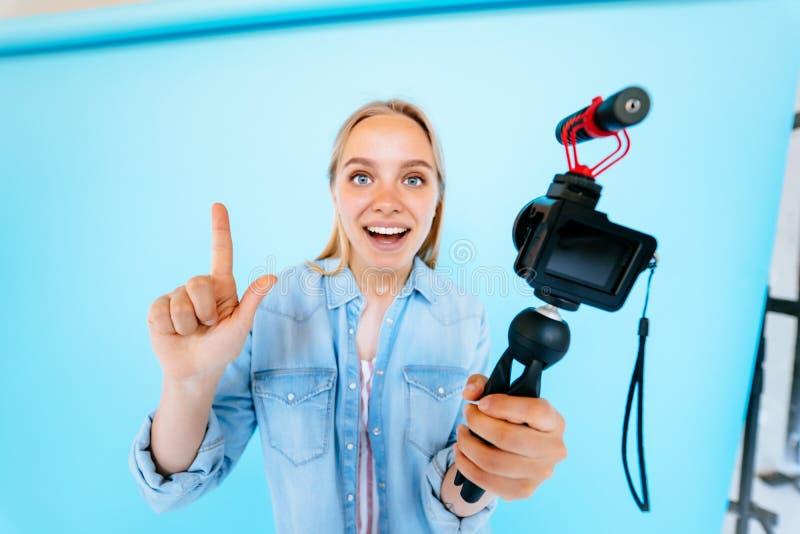 Piękny dziewczyny blogger ono uśmierza przy kamera odizolowywającym błękitnym tłem obraz royalty free