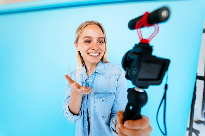Piękny dziewczyny blogger ono uśmierza przy kamery błękita tłem zdjęcia stock