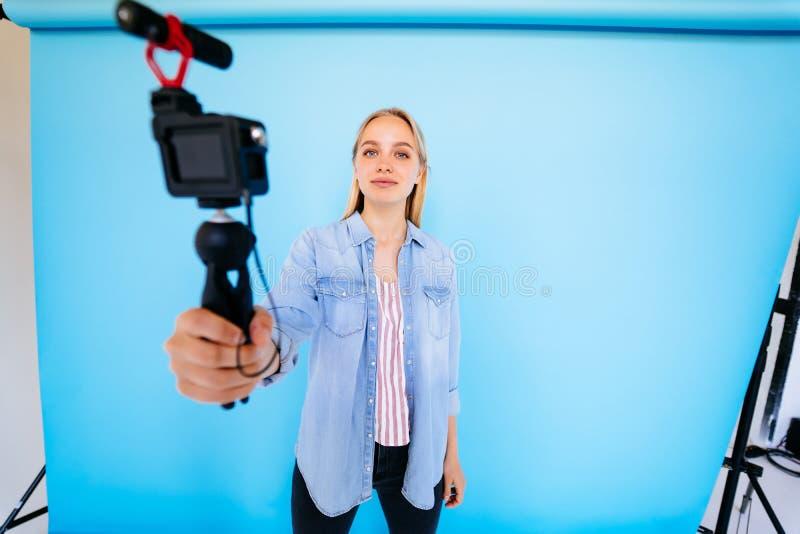 Piękny dziewczyny blogger ono uśmierza przy kamery błękita tłem zdjęcie stock