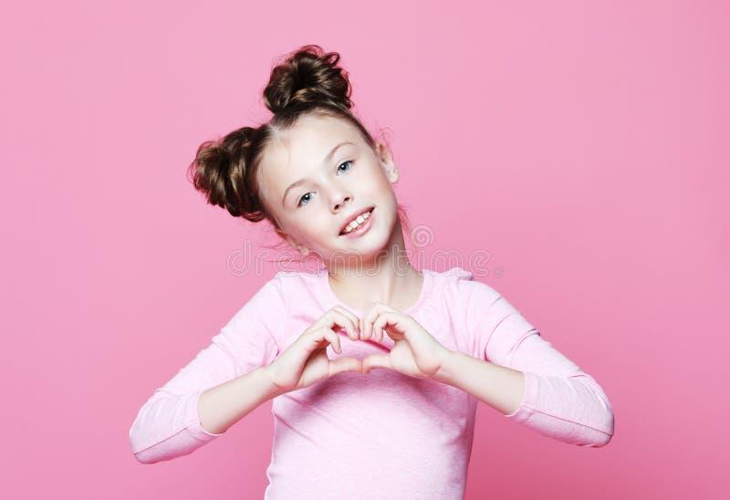 piękny dziewczyny dziecko ono uśmiecha się w miłości pokazuje kierowego symbol i kształt z rękami nad różowym tłem obrazy stock