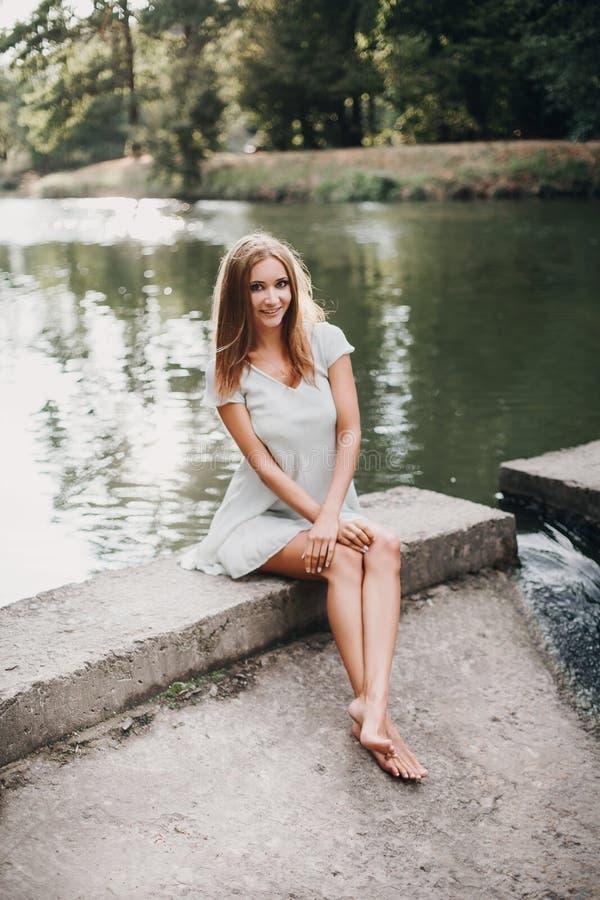Piękny dziewczyny obsiadanie blisko ono uśmiecha się i wody fotografia stock