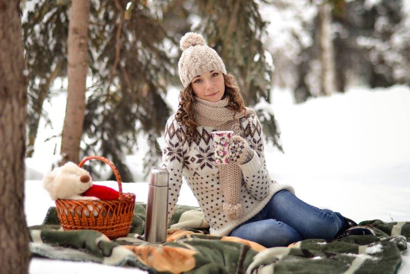 Piękny dziewczyny obsiadanie na koc w zimie w fosest i pije herbacie fotografia stock