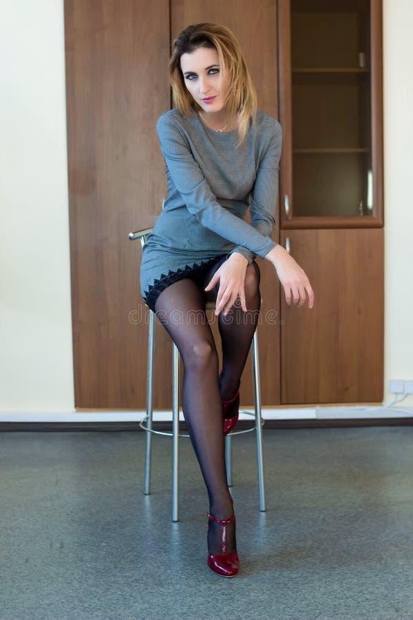 Piękny dziewczyny obsiadanie na krześle obrazy stock