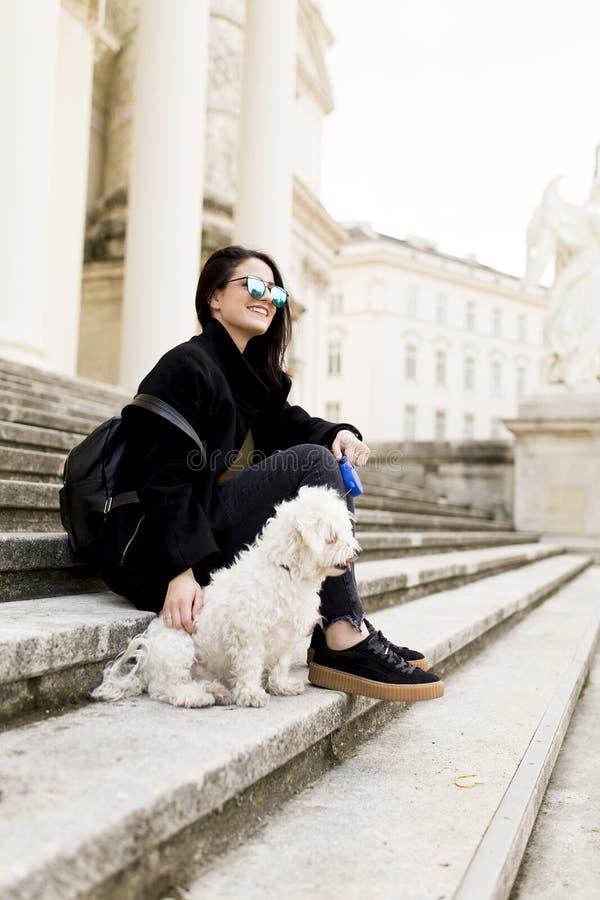 Piękny dziewczyny obsiadanie na schodkach z jej zwierzę domowe psem po spaceru wewnątrz zdjęcie royalty free