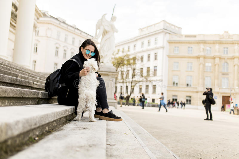 Piękny dziewczyny obsiadanie na schodkach z jej zwierzę domowe psem po spaceru wewnątrz fotografia royalty free