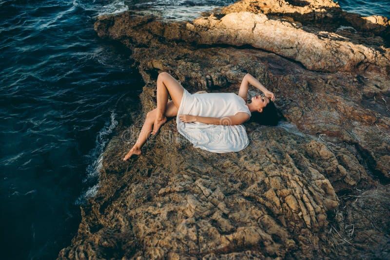 Piękny dziewczyny obsiadanie na skale na plażowym morzu zdjęcia royalty free