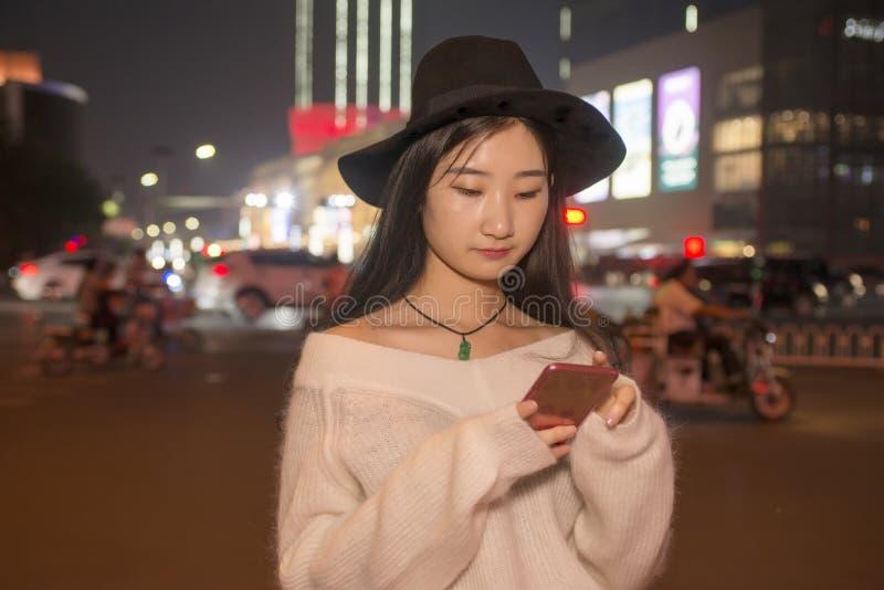 Piękny dziewczyny use telefon komórkowy w ulicach przy nocą zdjęcie royalty free