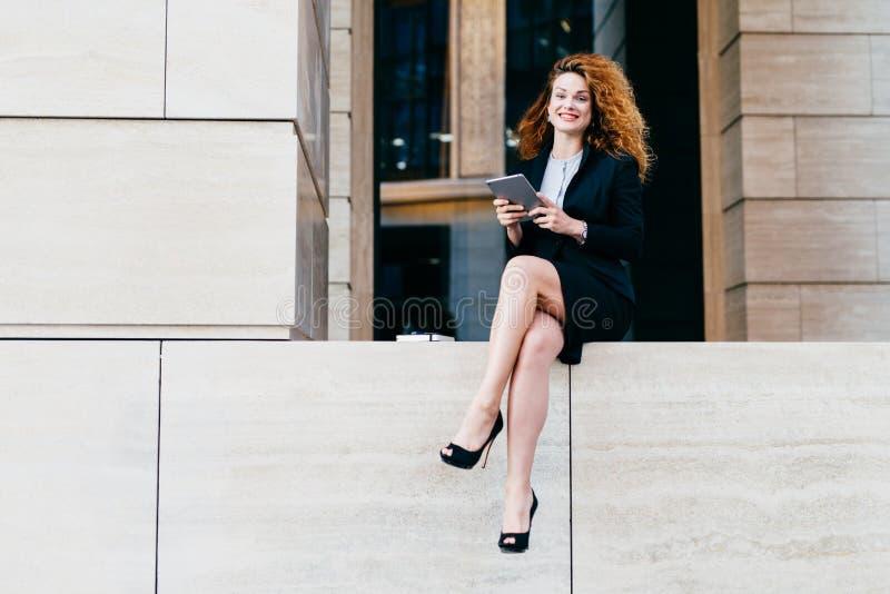 Piękny elegancki bizneswoman w formalnym odziewa buty i heeled, mieć falistego włosy i nikłe nogi, używać nowożytną pastylkę fo fotografia stock