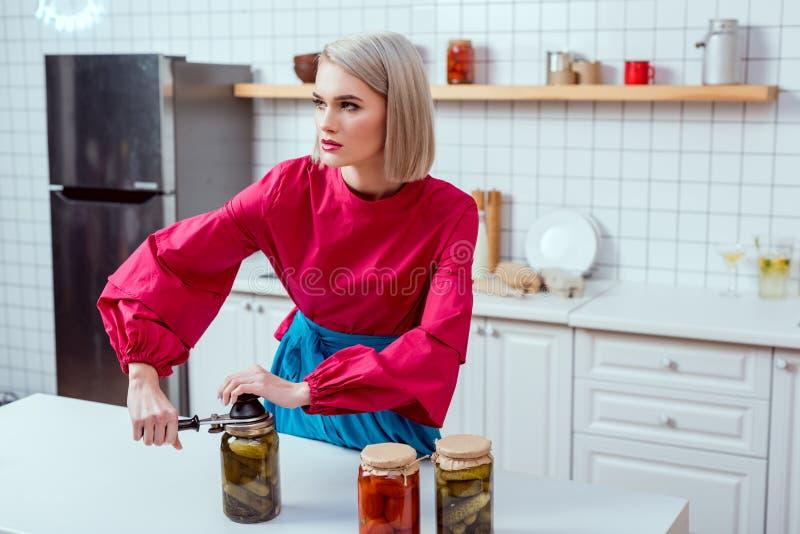 piękny elegancki gospodyni domowej lakowania słój kiszeni ogórki zdjęcia stock