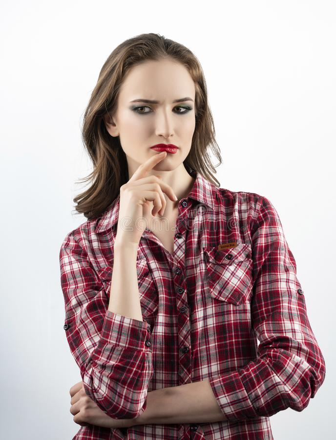 Piękny emocjonalny dziewczyna model z czerwonym warga makijażem, będący ubranym przypadkową szkockiej kraty koszula, cajgi marszc obrazy royalty free