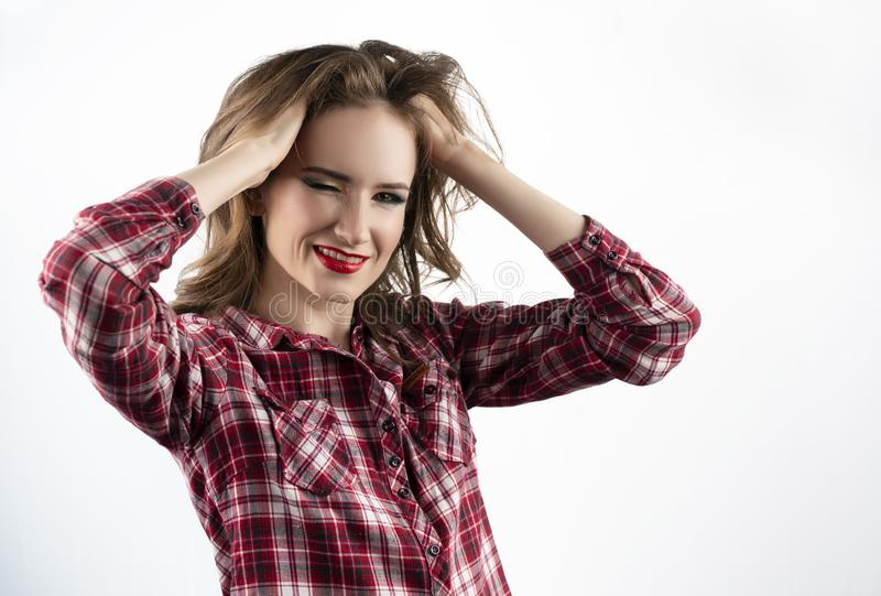 Piękny emocjonalny dziewczyna model z czerwonym warga makijażem, będący ubranym przypadkową szkockiej kraty koszula, cajgi i mrug zdjęcie stock