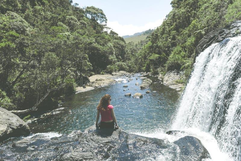 Piękny europejski turystyczny dziewczyny obsiadanie na krawędzi piekarzów spadków w Horton równiien parku narodowym zdjęcia stock