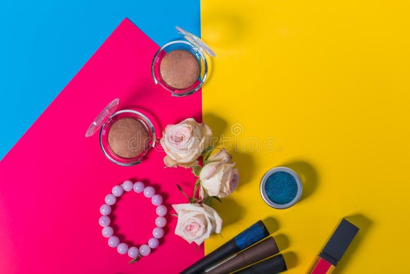 Piękny eyeshadow brąz, błękit, menchia rozpyla róże, bransoletka, jaskrawa menchia, żółty tło, zakończenie up, copyspace obrazy stock