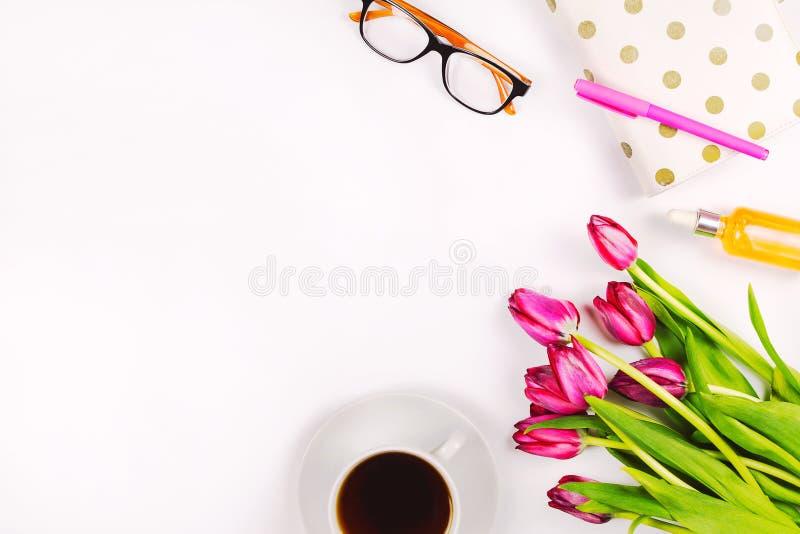 Piękny flatlay z tulipanami, filiżanką herbata, szkłami, notatnikiem i kosmetykami, obraz royalty free