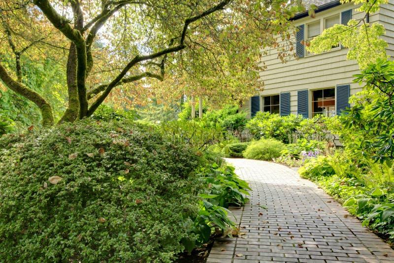 Piękny frontowy jard z przejściem i popielatym brown ampuła domem fotografia royalty free