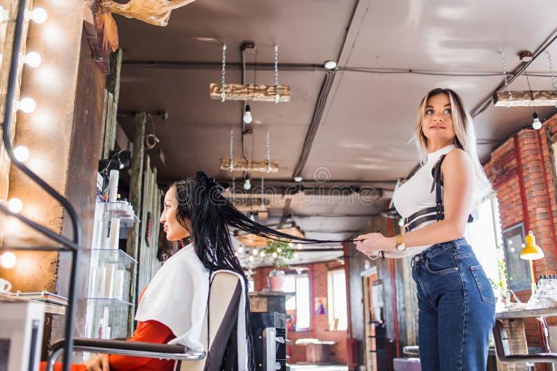 Piękny fryzjer podczas gdy pracujący z śliczną brunetki kobietą obraz stock