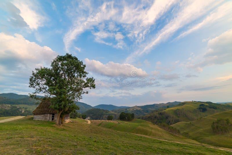 Piękny góra krajobraz z, stary dom, drzewa i chmurny ranku niebo, fotografia stock