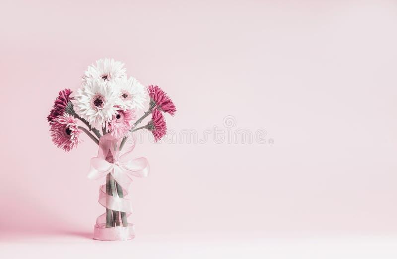 Piękny gerbera kwitnie wiązkę z tasiemkową pozycją na pastelowych menchii tle kosmos kopii zdjęcie stock