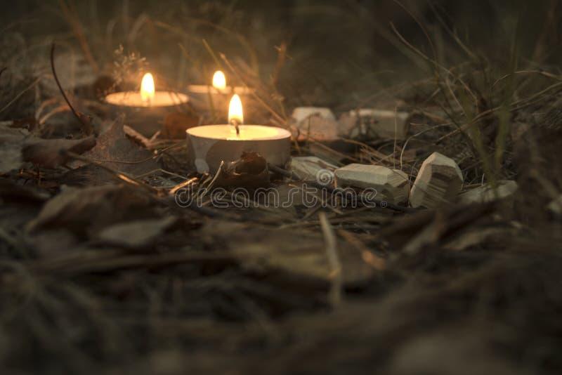Piękny Halloween skład z runes i świeczkami na trawie w ciemnym jesień lasu rytuale fotografia stock