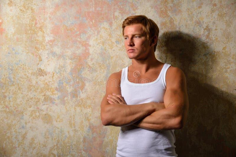 Piękny homoseksualista w białej koszulce pozuje przeciw grunge tłu obrazy stock