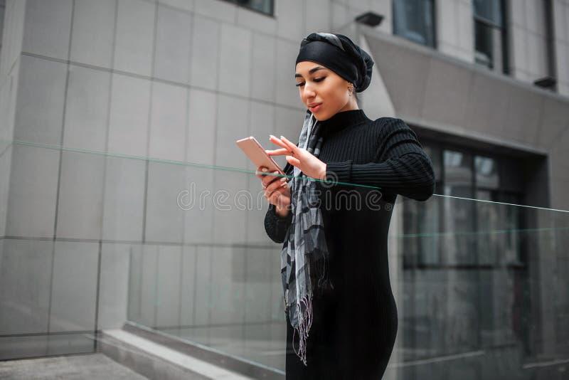 Piękny i atrakcyjny arabski kobieta stojak przy Trzyma na ręce blisko do Model jest ubranym zdjęcie royalty free