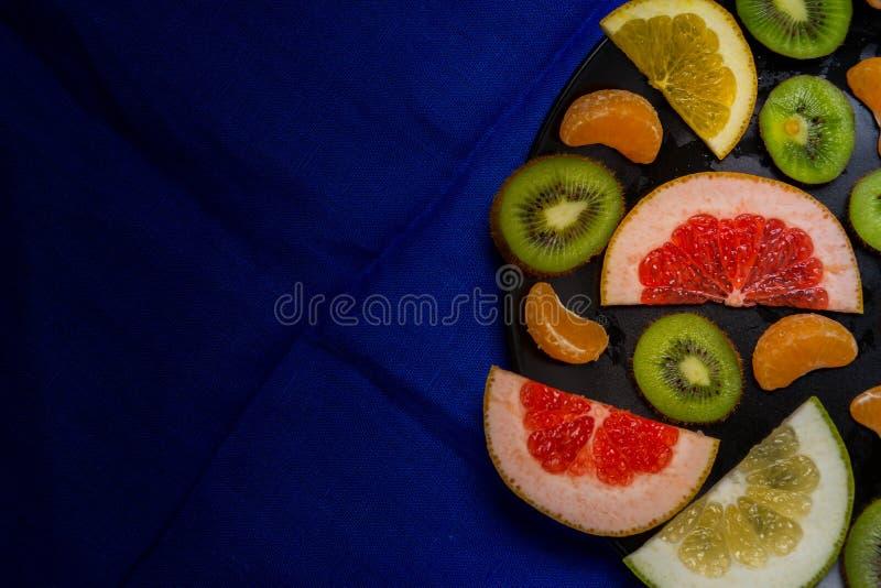 Piękny jaskrawy cytrus owoc cięcie w kawałków plasterki w ampuła talerza czerni kamienia ciemnego czerni popielatym tle z copyspa obrazy royalty free