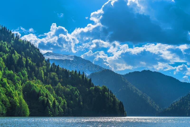 Piękny Jeziorny Ritsa w Kaukaz górach Zieleni halni wzgórza, niebieskie niebo z chmurami niebieska spowodowana pola pełne się chm fotografia stock
