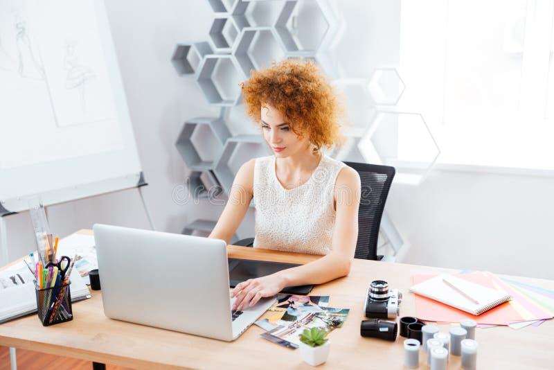 Piękny kędzierzawy młoda kobieta fotograf używa laptop z graficzną pastylką obraz royalty free
