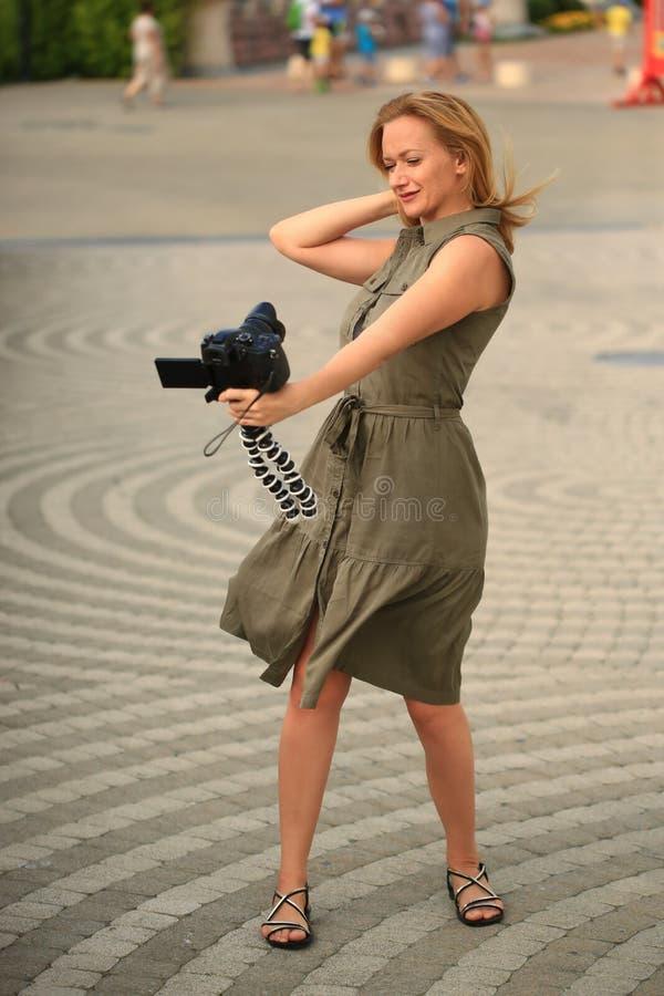 Piękny kobieta fotograf ono bierze z kamerą w parku rozrywki Szczęśliwy blogger robi śmiesznemu obrazkowi zdjęcia stock