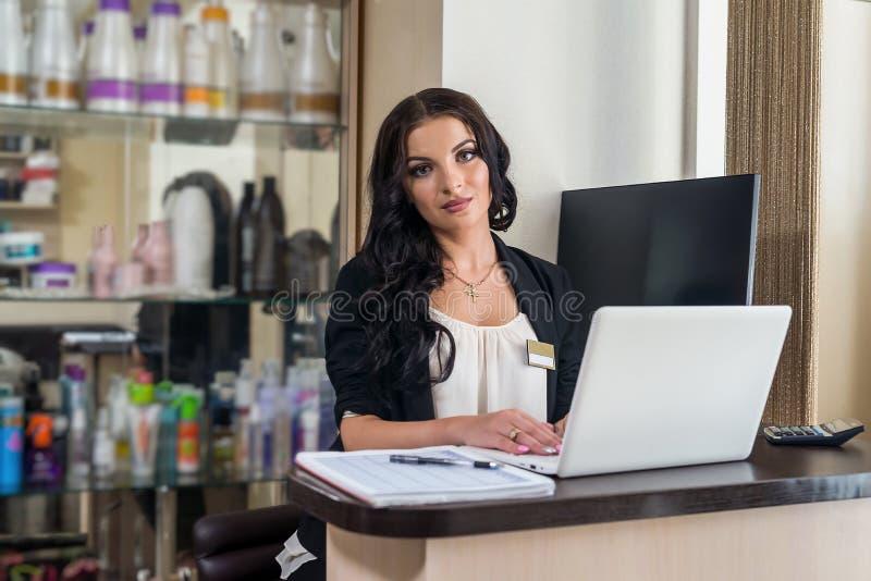 Piękny kobieta recepcjonista ono uśmiecha się przy jej miejsce pracy zdjęcie stock