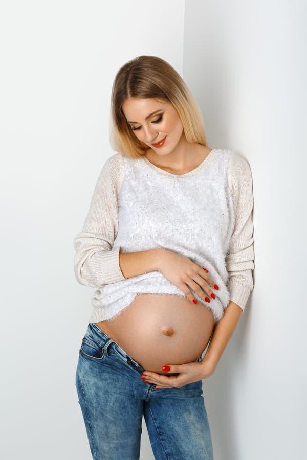 Piękny kobieta w ciąży w cajgach fotografia royalty free