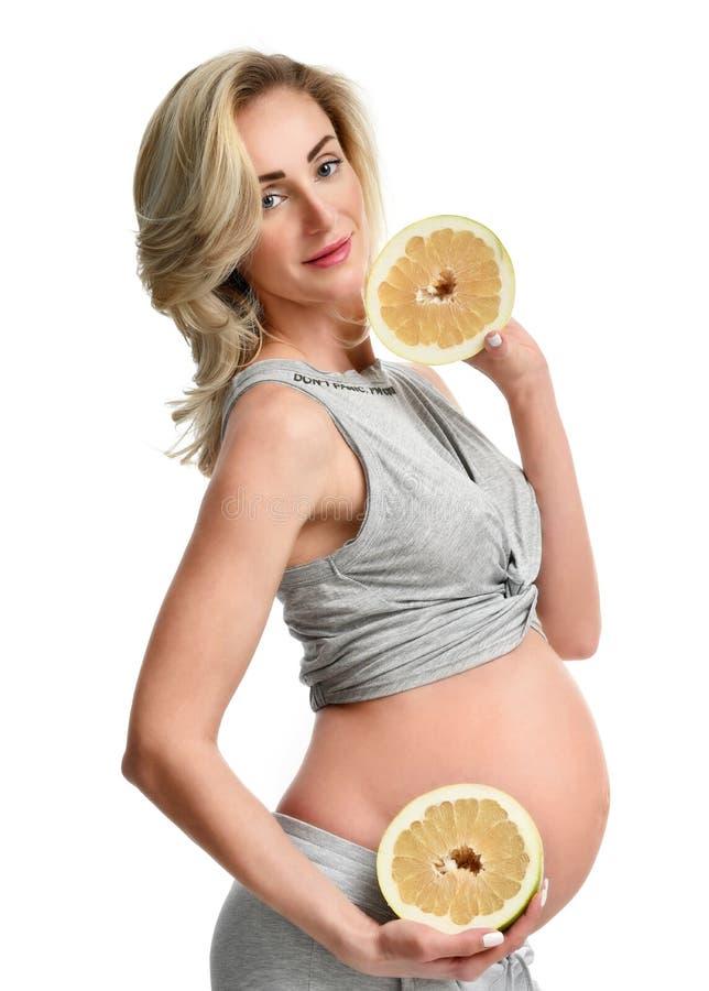 Piękny kobieta w ciąży chwyt dwa połówki pomelo owoc obraz stock
