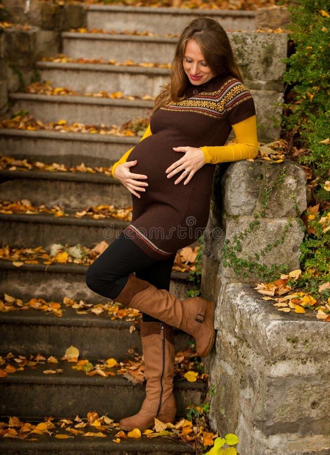 Piękny kobieta w ciąży plenerowy w parku na jesieni popołudniu z wibrującą naturą barwi w tle obrazy royalty free