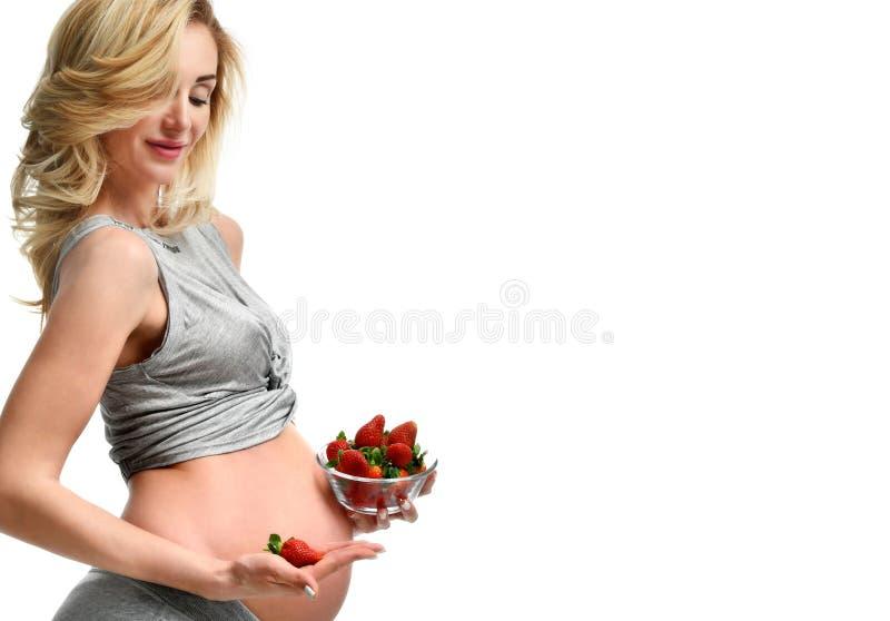 Piękny kobieta w ciąży z dużym brzuchem je strawberrie obrazy royalty free