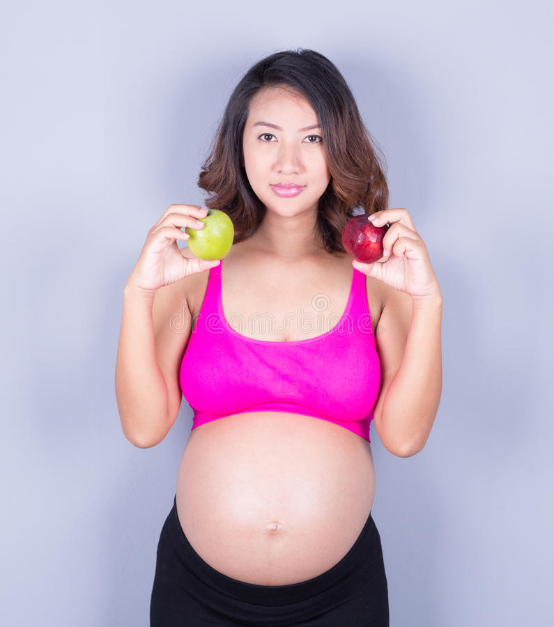 Piękny kobieta w ciąży z jabłkiem na szarym tle obraz royalty free