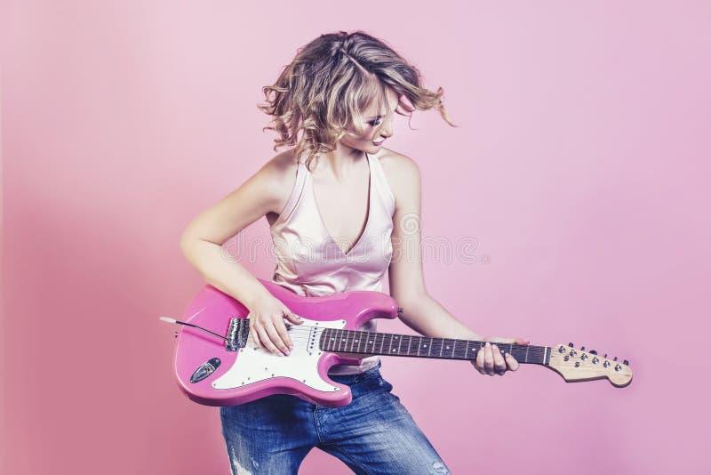 Piękny kobiety blondynki model z gitarą elektryczną i uzupełniał fa zdjęcia stock