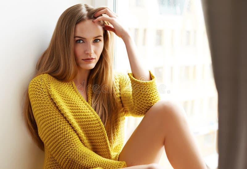 Piękny kobiety blondynki włosy siedzi następnego okno naturalnego makeup zdjęcie royalty free