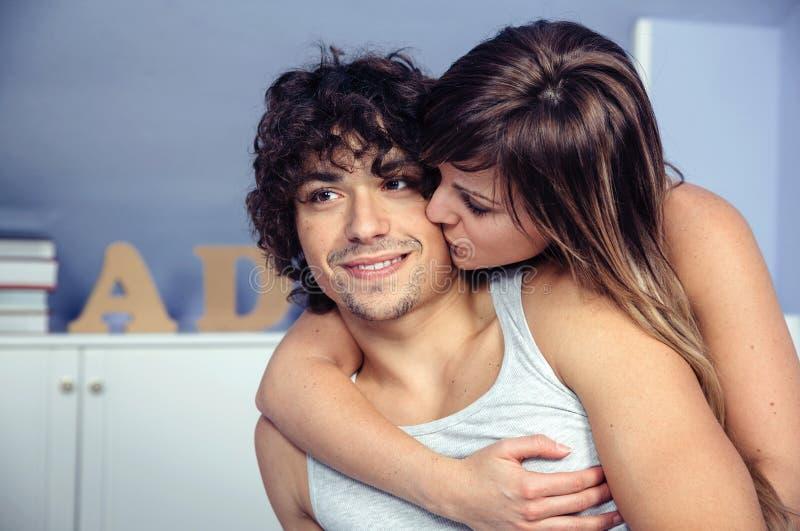 Piękny kobiety całowanie, obejmowanie szczęśliwy mężczyzna i obraz stock